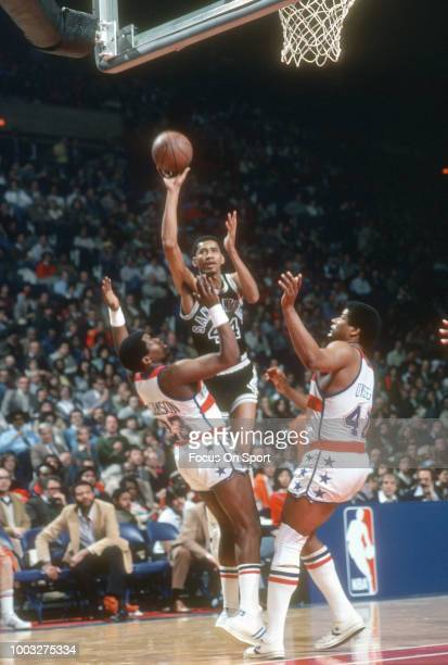 George Gervin of the San Antonio Spurs shoots over John Williamson and Wes Unseld of the Washington Bullets during an NBA basketball game circa 1980...