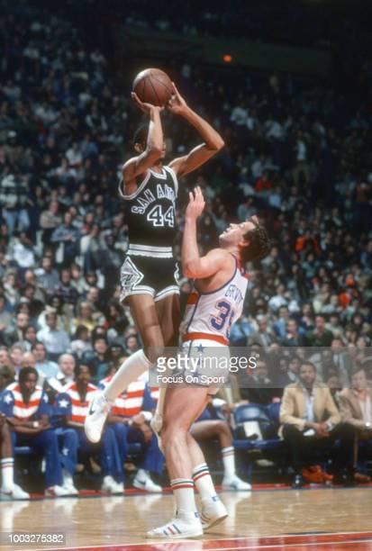 George Gervin of the San Antonio Spurs shoots over Kevin Grevey of the Washington Bullets during an NBA basketball game circa 1980 at the Capital...