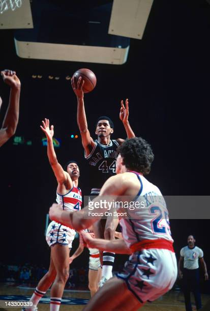 George Gervin of the San Antonio Spurs shoots over Phil Chenier and Mitch Kupchak of the Washington Bullets during an NBA basketball game circa 1978...