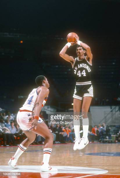 George Gervin of the San Antonio Spurs shoots over Rick Mahorn of the Washington Bullets during an NBA basketball game circa 1982 at the Capital...