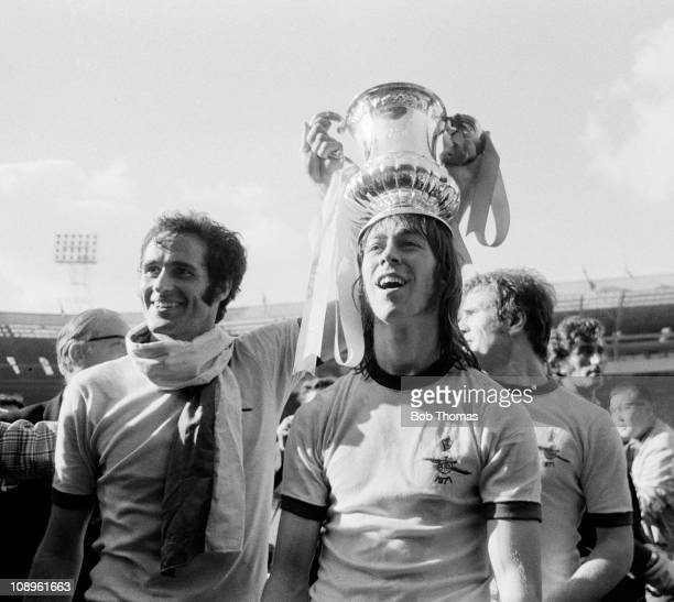 George Graham of Arsenal celebrates with teammate and winning goal scorer Charlie George after the Arsenal v Liverpool FA Cup Final held at Wembley...