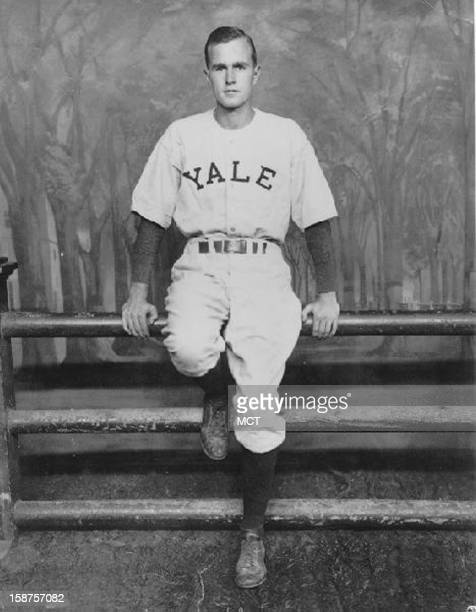 George H W Bush standing in front of a Yale Fence in his baseball uniform at Yale University circa 194548