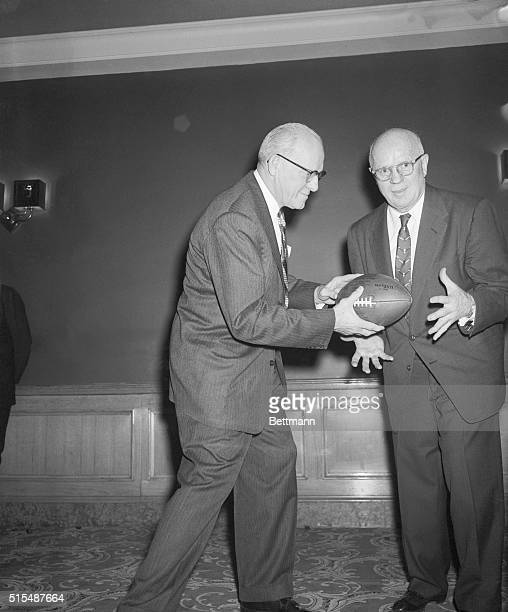 George Halas owner of the Chicago Bears hands over a football as well as head coaching job to John L Paddy Driscoll appointed by Halas who is...