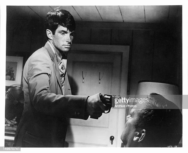 George Hamilton aiming gun at the head of Aldo Ray in a scene from the film 'The Power' 1968