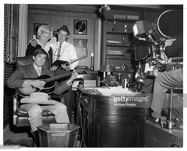 George Hamilton strums the guitar as Audrey Williams and director Gene Nelson watch in between scenes from the film 'Your Cheatin' Heart' 1964