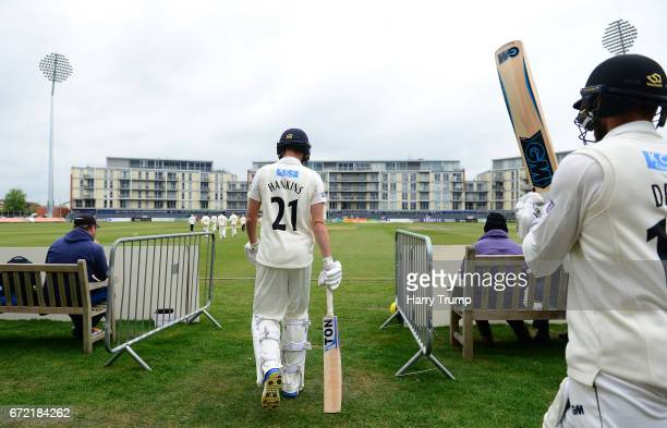 George Hankins and Chris Dent of Gloucestershire make their way out for the start of play during the Specsavers County Championship Division Two...