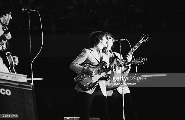George Harrison and John Lennon on stage during the Beatles concert at Tokyos Budokan Hall Japan 2nd July 1966 Paul McCartney is on the left