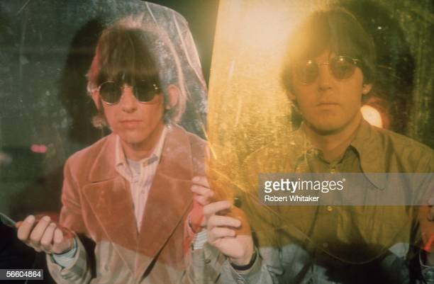 George Harrison and Paul McCartney of the Beatles looking through sheets of coloured plastic during the Paperback Writer/Rain sessions