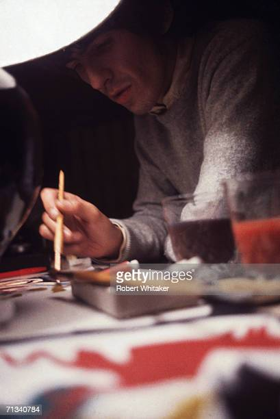 George Harrison at work on the Beatles collage 'Images of a Woman' at the Tokyo Hilton Japan during the band's tour of Asia 1966