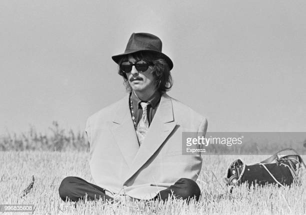 George Harrison , guitarist with the Beatles, pictured wearing an oversized jacket and a trilby hat during filming of 'Magical Mystery Tour' in a...