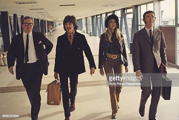 George Harrison guitarist with the Beatles pictured with his wife Pattie Boyd and two minders as they walk through a terminal at Heathrow Airport in...
