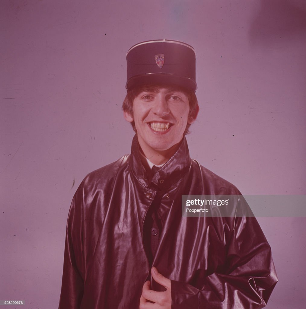 George Harrison (1943-2001) guitarist with the Beatles wears a kepi hat and leather coat in a studio in Paris in January 1964.