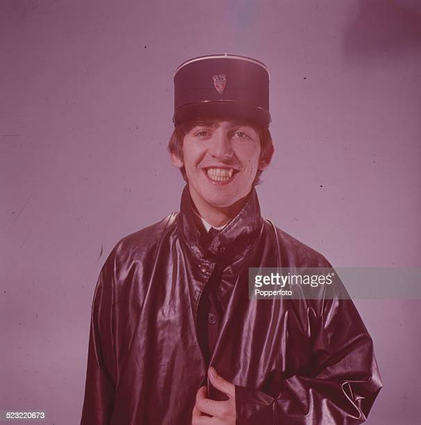 George Harrison guitarist with the Beatles wears a kepi hat and leather coat in a studio in Paris in January 1964