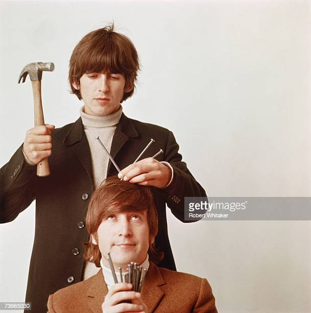 George Harrison in a playful pose about to knock a nail into the head of John Lennon during a studio session in Chelsea London March 1966