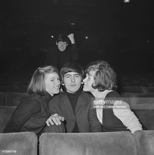 George Harrison of The Beatles enjoys the attentions of two fans as Paul McCartney shakes his fist in the background at the Gaumont Cinema Doncaster...