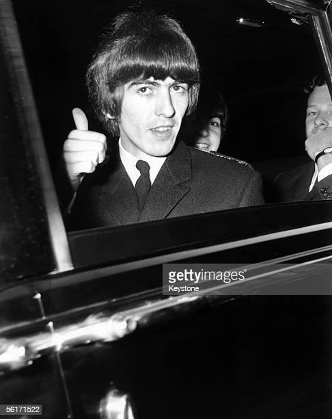 George Harrison of the Beatles gives a 'thumbs up' sign from his car window, whilst on his way to Buckingham Palace to collect an MBE, 26th October...