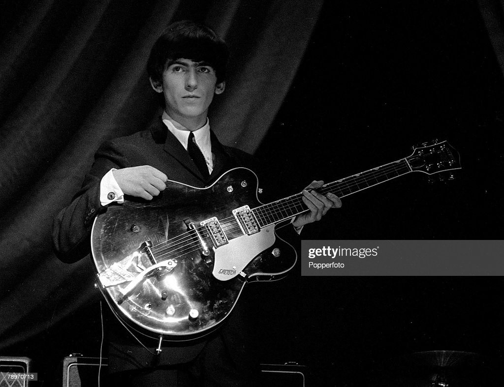 George Harrison of The Beatles pop group, holding his guitar during a rehearsal, 1963. : News Photo