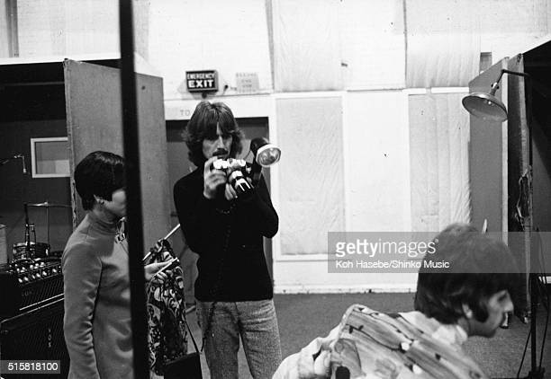 George Harrison of The Beatles setting up a borrowed camera during the recording session for the song 'The Fool On The Hill' at EMI Studios Abbey...
