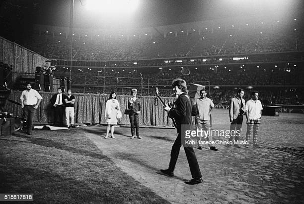 George Harrison of The Beatles walking towards the stage at Dodger Stadium Los Angeles California August 28