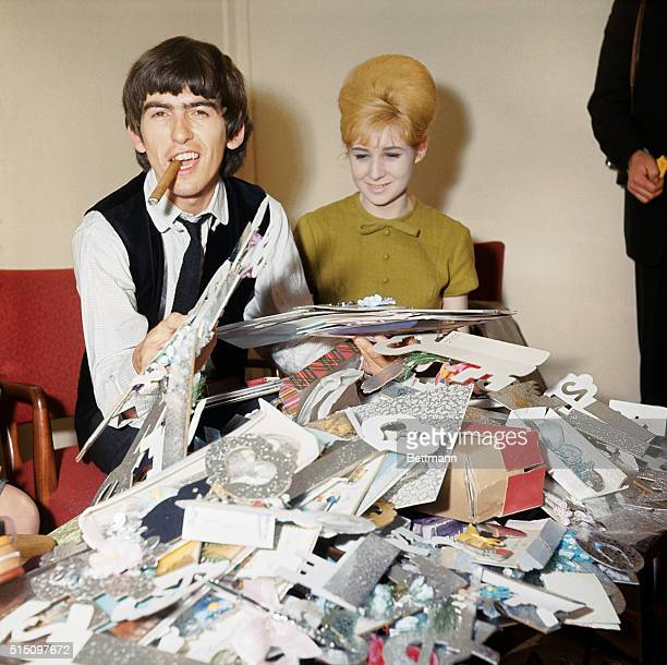 George Harrison smokes a cigar and holds birthday cards sent to him by fans. The young woman is from the Beatles' management company, NEMS, and was...