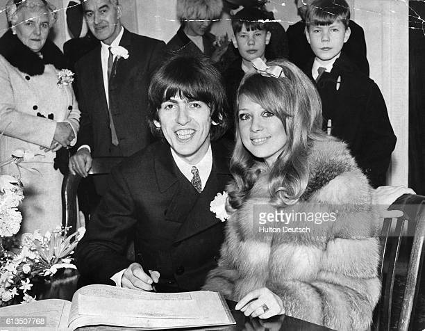 George Harrison, the British rock singer, guitarist, composer, and member of The Beatles signs the register with his wife, the English model Patti...