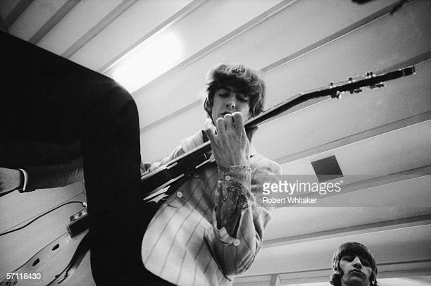 George Harrison warms up for a matinee concert backstage at the Nippon Budokan in Tokyo during the Beatles' Asian tour 2nd July 1966 Beatles drummer...