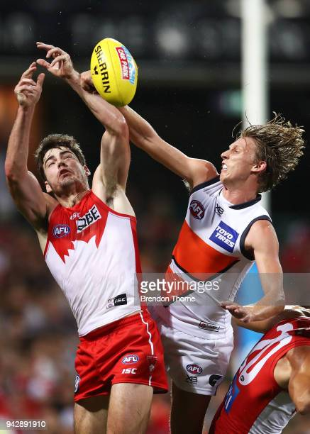 George Hewett of the Swans contests the ball with Lachie Whitfield of the Giants during the round three AFL match between the Sydney Swans and the...