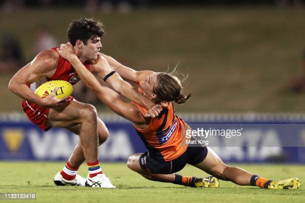 George Hewett of the Swans is challenged by Harry Himmelberg of the Giants during the 2019 JLT Community Series AFL match between the Greater Western...