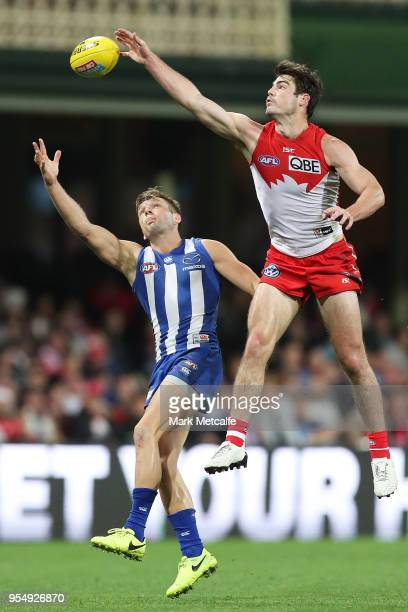 George Hewett of the Swans punches the ball ahead of Ben Jacobs of the Kangaroos during the round seven AFL match between the Sydney Swans and the...