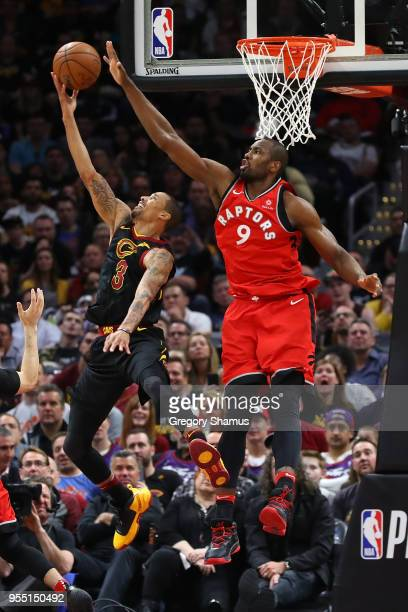 George Hill of the Cleveland Cavaliers tries to get a second half shot off past Serge Ibaka of the Toronto Raptors during Game Three of the Eastern...