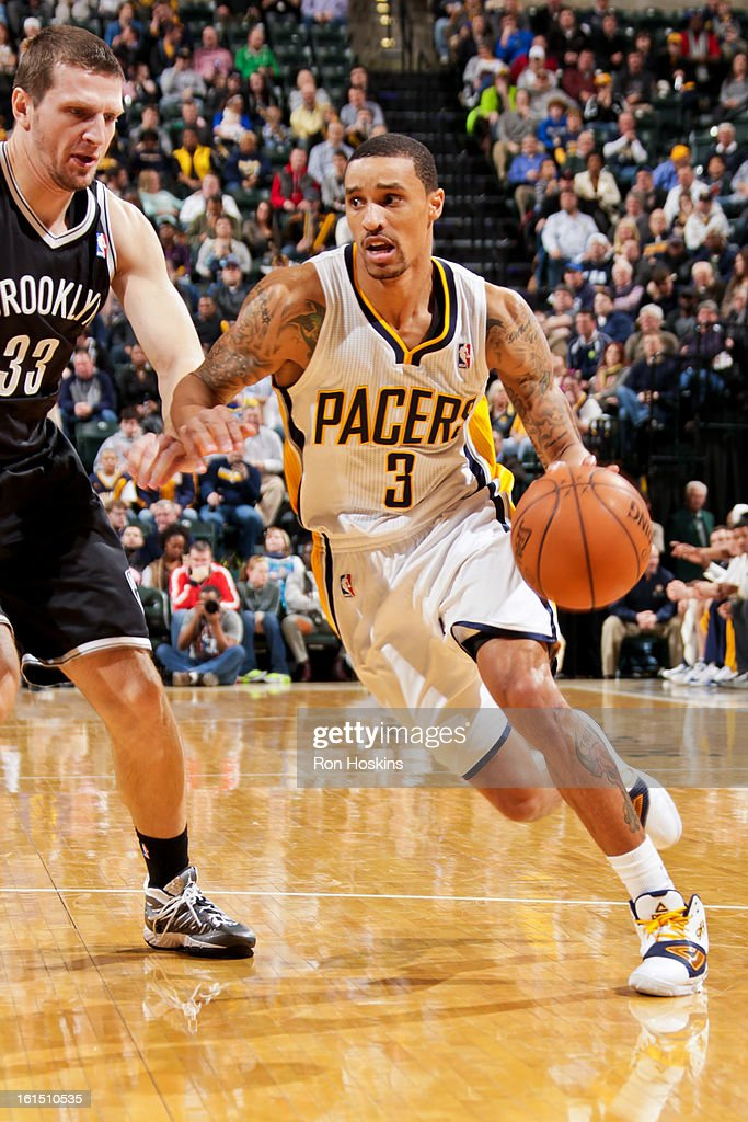 George Hill #3 of the Indiana Pacers drives against Mirza Teletovic #33 of the Brooklyn Nets on February 11, 2013 at Bankers Life Fieldhouse in Indianapolis, Indiana.