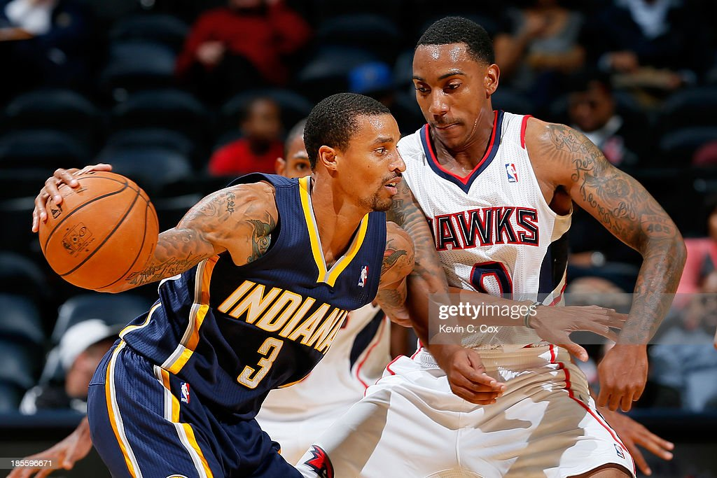 George Hill #3 of the Indiana Pacers drives into Jeff Teague #0 of the Atlanta Hawks at Philips Arena on October 22, 2013 in Atlanta, Georgia.