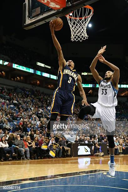 George Hill of the Indiana Pacers goes to the basket against Adreian Payne of the Minnesota Timberwolves on December 26 2015 at Target Center in...
