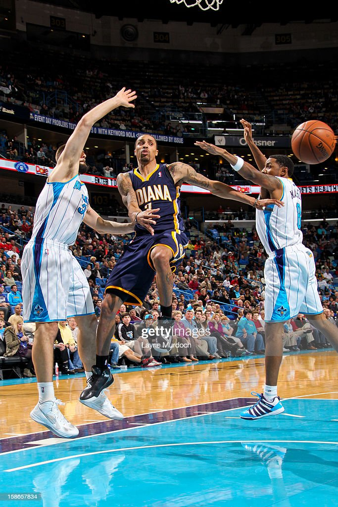 George Hill #3 of the Indiana Pacers passes the ball in the lane against Roger Mason Jr. #8 and Ryan Anderson #33 of the New Orleans Hornets on December 22, 2012 at the New Orleans Arena in New Orleans, Louisiana.