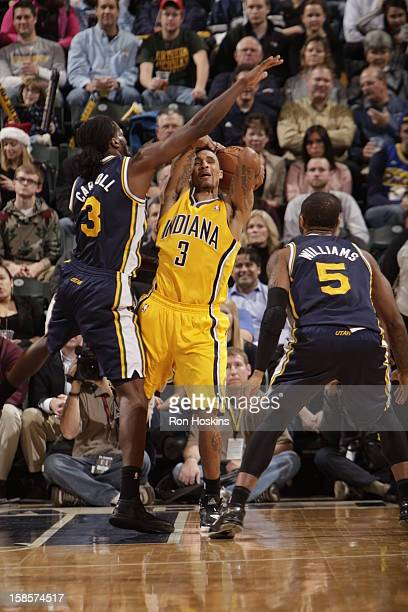 George Hill of the Indiana Pacers shoots the ball over DeMarre Carroll of the Utah Jazz and Mo Williams of the Utah Jazz during the game between the...