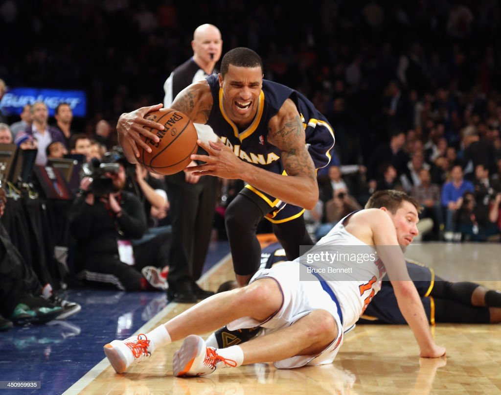 George Hill #3 of the Indiana Pacers trips over Beno Udrih #18 of the New York Knicks at Madison Square Garden on November 20, 2013 in New York City.