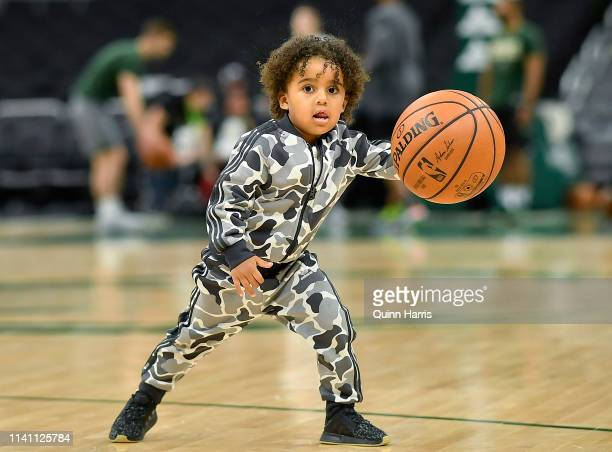 George Hill of the Milwaukee Bucks and plays basketball with his son before the game against the Brooklyn Nets at Fiserv Forum on April 06 2019 in...