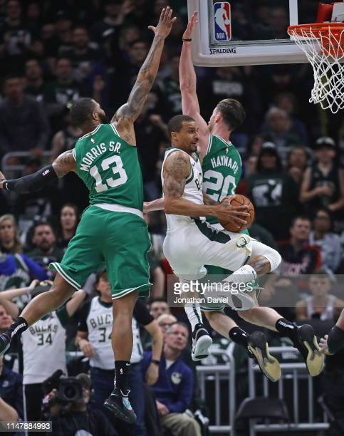 George Hill of the Milwaukee Bucks drives to the basket between Malcolm Brogdon and Gordon Hayward of the Boston Celtics at Fiserv Forum on May 08...