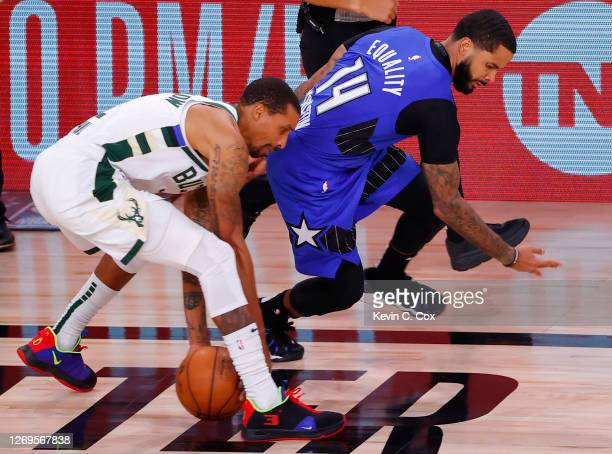 George Hill of the Milwaukee Bucks saves a loose ball against D.J. Augustin of the Orlando Magic during the third quarter in Game Five of the Eastern...