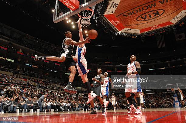 George Hill of the San Antonio Spurs makes a pass around Chris Kaman of the Los Angeles Clippers at Staples Center on November 17 2008 in Los Angeles...