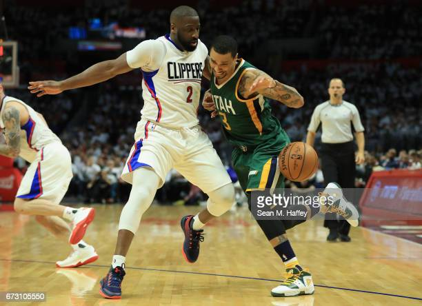 George Hill of the Utah Jazz dribbles into Raymond Felton of the Los Angeles Clippers during the second half of Game Five of the Western Conference...