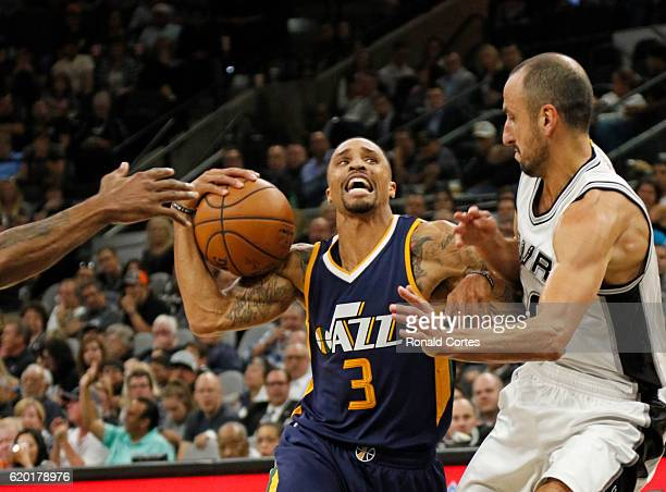 George Hill of the Utah Jazz drives on Manu Ginobili of the San Antonio Spurs during game between Utah Jazz and the San Antonio Spurs at ATT Center...