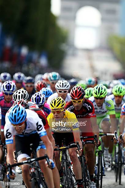 George Hincapie watches his teammate Cadel Evans yellow jersey wearere as they race during the twenty first and final stage of Le Tour de France 2011...