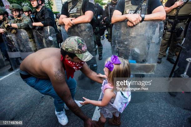 George Holland hugs three year-old Mikaela LG, of Tennessee during the 6th day of protests in Washington, D.C. After the death of George Floyd...