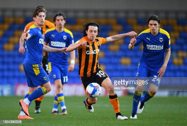 George Honeyman of Hull City breaks past Alex Woodyard and George Dobson of AFC Wimbledon during the Sky Bet League One match between AFC Wimbledon...