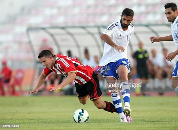 George Honeyman of Sunderland challenges Menosse of Recreativo during a pre season friendly match between Recreativo du Huelva and Sunderland at the...