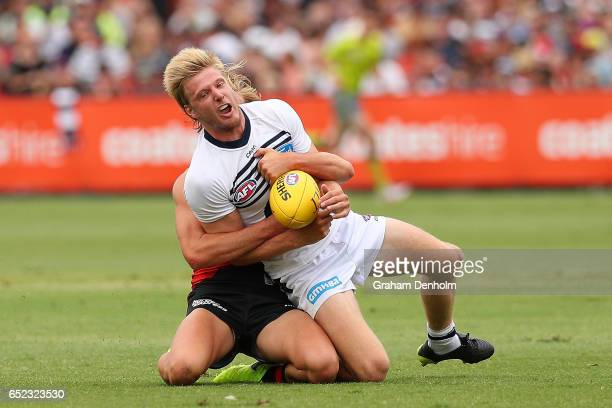George Horlin-Smith of the Cats is tackled during the JLT Community Series AFL match between the Geelong Cats and the Essendon Bombers at Queen...