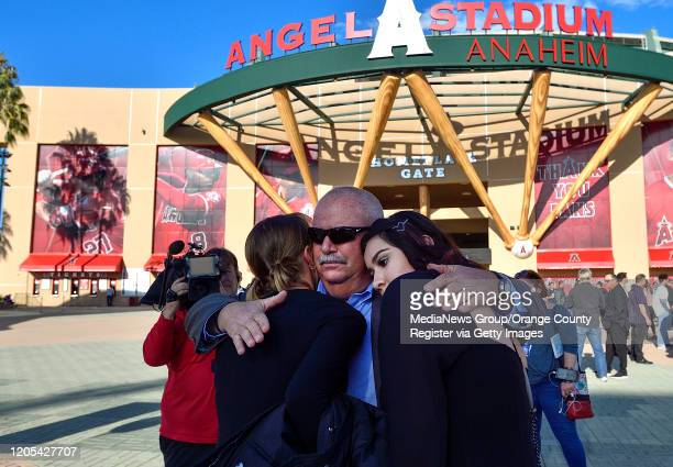 George Horton center hugs his grand daughters Kaile Cook left and Alyssa Ortega outside Angel Stadium before a memorial service for the Altobelli...