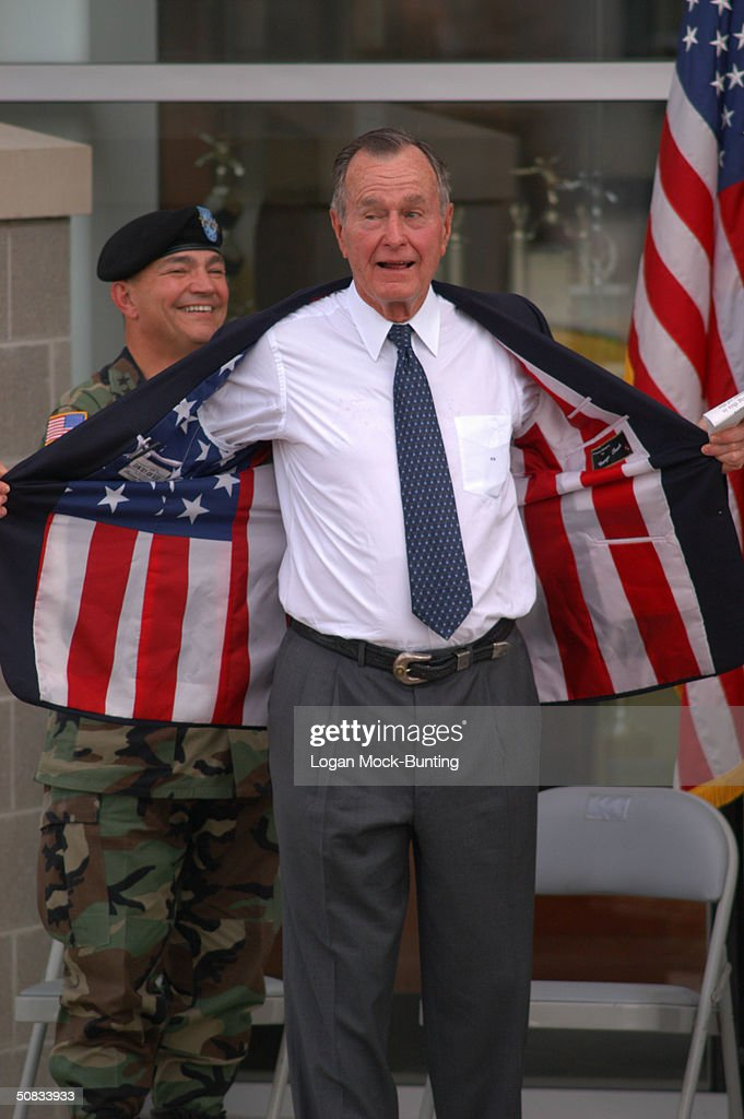 George H.W. Bush, 41st President of the United States, flashes the inside of his jacket, containing an American flag, at the Brigadier General Joseph Stilwell Headquarters dedication ceremony May 13, 2004 in Fort Bragg, North Carolina. The headquarters contains history awards and exhibits on the Golden Knights, the U.S. Army Parachute Team.