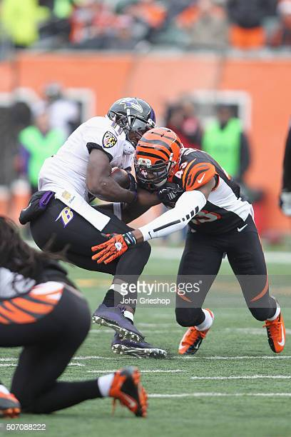 George Iloka of the Cincinnati Bengals tackles Kamar Aiken of the Baltimore Ravens during their game at Paul Brown Stadium on January 3 2016 in...